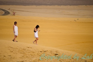 สองสาวนักท่องเที่ยวเดินชมความงามของทะเลทรายริมฝั่งมหาสมุทรของปารากัส