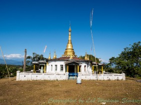 A golden pagoda on a hill in Putao